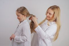 Mom and daughter in white shirts with long blonde hair posing on a solid background in the Studio. a charming family takes care of. Each other and makes braids royalty free stock photos