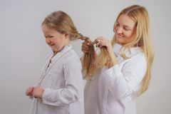 Mom and daughter in white shirts with long blonde hair posing on a solid background in the Studio. a charming family takes care of. Each other and makes braids stock photos