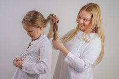 Mom and daughter in white shirts with long blonde hair posing on a solid background in the Studio. a charming family takes care of royalty free stock photos