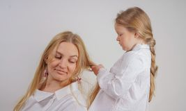 Mom and daughter in white shirts with long blonde hair posing on a solid background in the Studio. a charming family takes care of. Each other and makes braids stock images