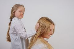 Mom and daughter in white shirts with long blonde hair posing on a solid background in the Studio. a charming family takes care of. Each other and makes braids royalty free stock photography