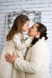 Mom and daughter in the winter dresses Royalty Free Stock Photos
