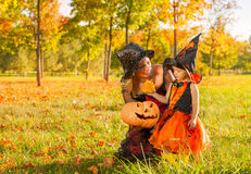 Mom and daughter in witches costumes with pumpkin Royalty Free Stock Images