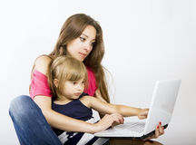 Mom and daughter working on laptop. Mother and daughter using laptop computer Stock Images