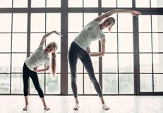 Mom with daughter working out at home. Attractive young mom with her little charming daughter are working out at home. Stretching indoors together. Fitness day Stock Photo