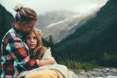 Mom with daughter wrapped in blanket. Mom with daughter wrapped in warm blanket outdoor, hiking in mountains, bad cold weather with fog Royalty Free Stock Images