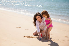 Mom and daughter writing in sand Stock Photography