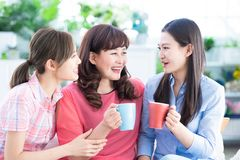 Mom and daughters drink together stock photography