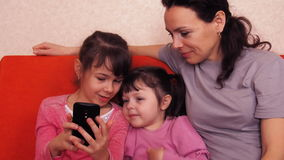 Mom and daughters play with a mobile phone. Happy family playing in mobile phone. Mom with two daughters stock footage