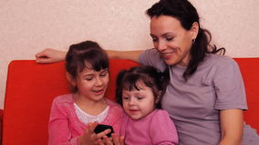 Mom and daughters play with a mobile phone. Happy family playing in mobile phone. stock video footage