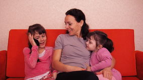 Mom and daughters play with a mobile phone. Happy family playing in mobile phone. stock video
