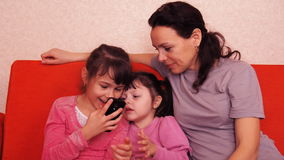 Mom and daughters play with a mobile phone. Happy family playing in mobile phone. Mom with two daughters stock video footage