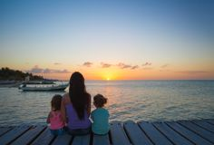 Mom and daughters silhouette in the sunset on the Stock Photos