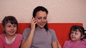 Mom and daughters are talking on the mobile. Happy family talking on mobile phone. stock video footage
