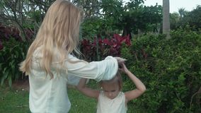 Mom decorates daughter`s hair with flowers of Plumeria slow motion stock footage video stock video