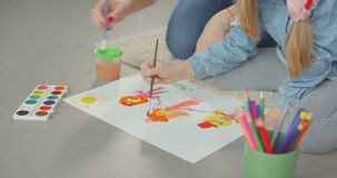 Mom developing creativity of child through painting. Close-up of hands of caring mother and elementary age daughter painting together on white paper while stock footage