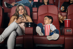 Mom distracted with phone at the movies Stock Photos