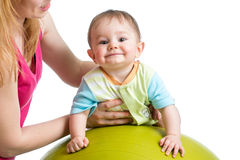 Mom doing gymnastics to her baby on fitness ball Stock Photos