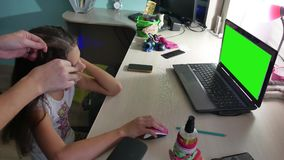 Mom doing a hairstyle to her daughter a teenager girl playing on a laptop indoor stock video