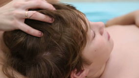 Mom is doing a head massage to her son. Beautiful thick hair stock footage