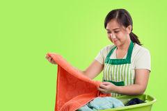 Mom doing laundry. Young Asian mother handwash laundry, over bright green background with copyspace Royalty Free Stock Image