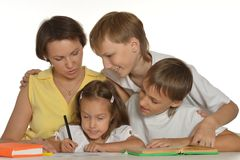 Mom drawing with her kids. A beautiful Caucasian mom with her daughter and sons sitting at the table with a penci Stock Photos