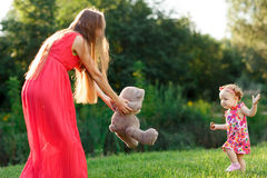 Mom in dress takes bear little daughter in summer park Stock Photo
