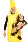 Mom dressed as banana with monkey baby smile. A mom in her banana costume with a smile, holding on to her little baby in her monkey costume Stock Images