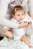 Mom dressing up baby. Cute baby girl getting dressed by mom while holding the foot with the hand Stock Images