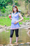 Mom drinking juice relex time in the river.  Royalty Free Stock Photo