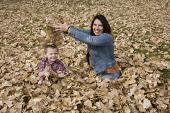 Mom droping leaves on son Royalty Free Stock Photo