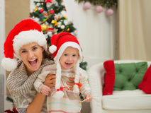 Mom and eat smeared baby girl in Christmas hats Royalty Free Stock Photography