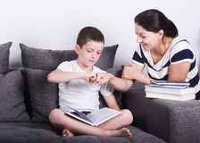 Mom encourages his son for reading a book. Studio portrait on white background Royalty Free Stock Image