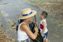 Mom entertains her son while playing guitar Royalty Free Stock Images