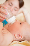 Mom feed baby with bottle Stock Photo