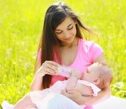 Mom feeding baby bottle outdoors. Happy mom feeding baby bottle outdoors royalty free stock images