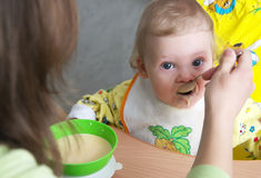 Mom feeding baby cereal. From a spoon Stock Photography