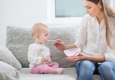 Mom feeding baby indoor Stock Images
