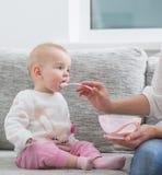 Mom feeding baby indoor Royalty Free Stock Photography