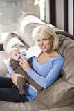 Mom feeding bottle to baby at home on couch Stock Photos