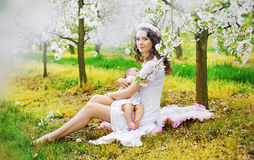 Mom feeding a child in the fragrant orchard Stock Photo