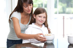 Mom feeding daughter breakfast cereal. An attractive young mom feeding cute daughter healthy breakfast cereal in the morning Stock Image