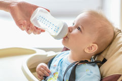 Mom is feeding her baby a bottle of milk Stock Photo