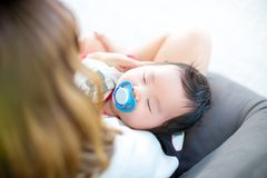 Mom feeding her baby daughter infant from bottle Adorable baby with a milk bottle. Baby milk eating bottle Royalty Free Stock Images