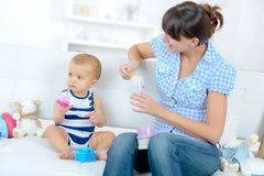 Mom feeding baby at home. Mom feeding her baby at home stock photos