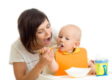 Mom feeding her kid boy Stock Images