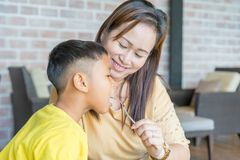 Mom is feeding her son with a smile. In the room royalty free stock image