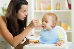 Mom feeding hungry baby in the highchair indoors Royalty Free Stock Photos