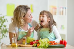 Mom feeding kid daughter vegetables in kitchen Royalty Free Stock Photos