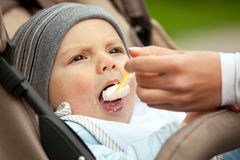 Mom feeding one-year old boy sitting in stroller Royalty Free Stock Photo